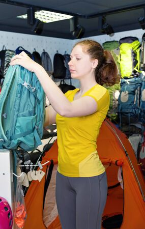 gamme de produit: Young caucasian girl in the yellow shirt is considering travel backpack in the store. Specialized products for tourism and mountaineering. The buyer on background of a display of tents and backpacks Banque d'images