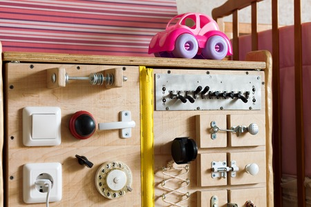 montessori: Playground structure of wood in the room. Toy with switches, buttons and levers. handmade Bizibord. Developing board motor skills of the child. Methods of Montessori. A room with toys for girls. Stock Photo