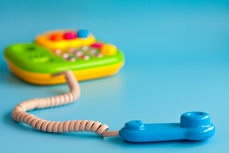 toy phone: Childrens toy phone with a tube of plastic on a blue background. Call on the phone. Copy space.