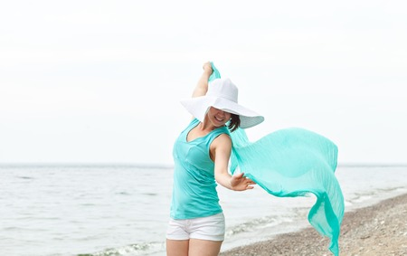 scarf beach: Portrait of a beautiful woman with a turquoise scarf and a big white hat on the beach enjoying the summer. Jumping on the beach. Freedom Concept. Travel and Leisure.