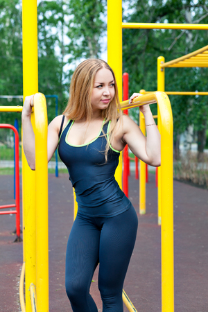 sexy young girl: sexy young fitness girl on the street gym. Blond fitness woman in sportswear with a perfect body fitness workout on the street to do the exercises on the horizontal bar