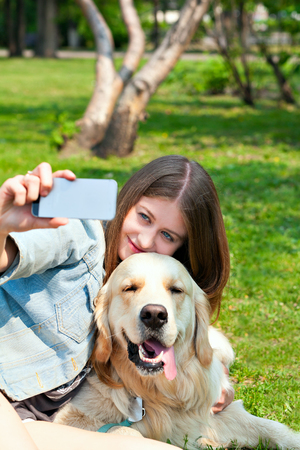 Owner woman with a golden retriever dog portrait taking selfie smartphone on a summer day outdoors