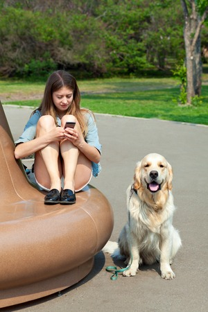 Portrait of a young girl with a smartphone in the hands on a park bench, next to her dog in the open vozduhe.Vladelets sitting next to his dog breed golden retriever on a background of summer city. Human friendship and dogs. Joint pastime.