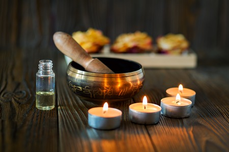 Singing bowl on dark wooden background. Burning candles and oil for aromatherapy and massage.
