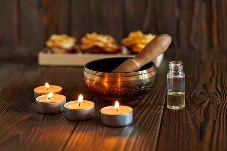 Zingende kom op donkere houten achtergrond. Brandende kaarsen en olie voor aromatherapie en massage Stockfoto