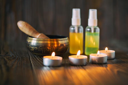 singing bowl massage: Burning candles and oil for aromatherapy and massage. Singing bowl on dark wooden background.