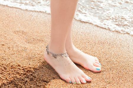 close-up van de benen en een sieraad voor uw voeten. Jonge volwassen vrouw voeten en tenen, het dragen van enkelbandje enkelband rusten in een zomervakantie reis. Stockfoto