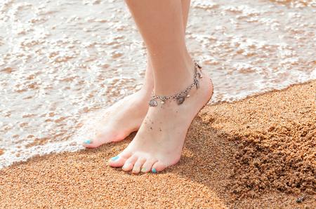 close-up der Beine und ein Schmuckstück für Ihre Füße. Junge erwachsene Frau Füße und Zehen, Fußkettchen Fußfessel ruht in einem Sommerferienreise zu tragen.