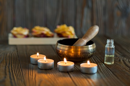 ancient yoga: singing bowl on dark wooden background. Burning candles and oil for aromatherapy and massage.. Stock Photo