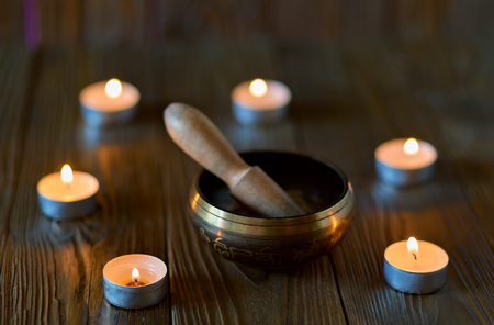 singing bowl on dark wooden background. Burning candles and oil for aromatherapy and massage.. Stock Photo