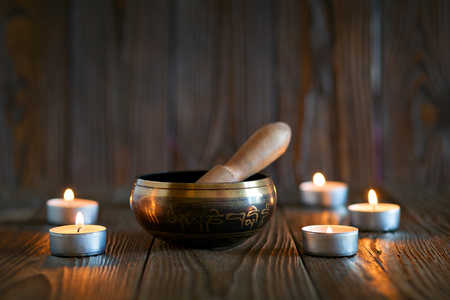 bronze bowl: singing bowl on dark wooden background. Burning candles and oil for aromatherapy and massage.. Stock Photo