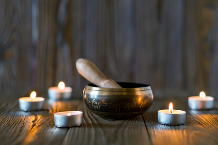 sound healing: singing bowl on dark wooden background. Burning candles and oil for aromatherapy and massage.. Stock Photo