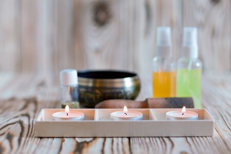 singing bowl massage: singing bowl on dark wooden background. Burning candles and oil for aromatherapy and massage.. Stock Photo