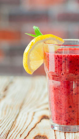 Fresh Fruit Smoothie berry. A glass of red smoothie with orange and mint on a wooden table. smoothie concept