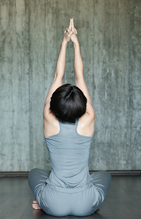 Young woman practicing yoga on a background of gray concrete wall. Urban background. Monochrome image. Stock Photo