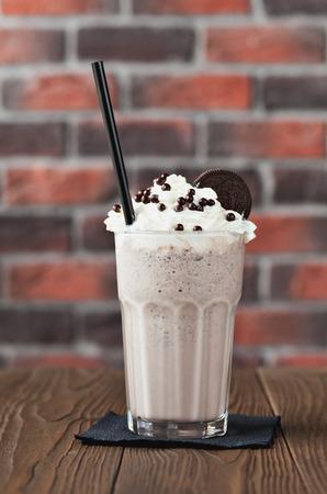 Chocoladekoekjes en room, melkchocoladecocktail in een groot glas op een houten achtergrond