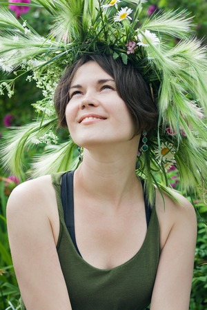 Portrait of a smiling beautiful girl in a wreath of flowers and herbs on the meadow on a sunny day. A young Slavic woman. Portrait of a young beautiful woman in wreath of wild flowers.