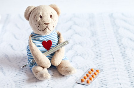 stuff toy: childrens soft toy teddy bear with pills takes the temperature of a mercury glass thermometer. childs disease. Stock Photo