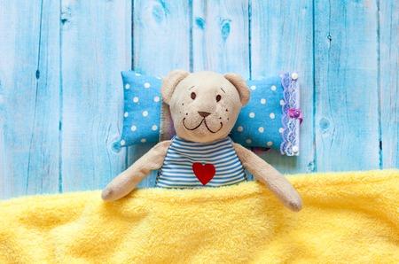 zacht kinderspeelgoed teddybeer in bed met een thermometer en pillen, nemen de temperatuur van een kwik glazen thermometer. Op een blauwe houten achtergrond met een gele deken. Het spelen in het ziekenhuis.