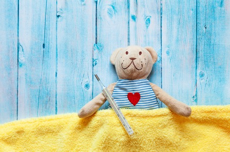 teething: childrens soft toy teddy bear in bed with thermometer and pills, take the temperature of a mercury glass thermometer. On a blue wooden background with a yellow blanket. Playing in hospital.