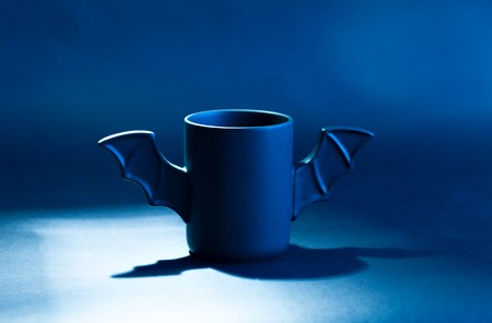 easel: A cup of coffee as a bat for Halloween on black background. Blue light and shadow. Toy bat. Halloween concept