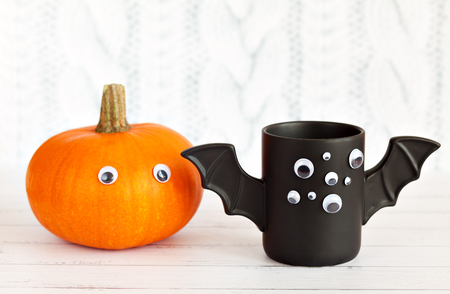 A cup of coffee like a bat with eyes on Halloween on a white background. Pumpkin with eyes. Toy bat. Halloween concept Stock Photo