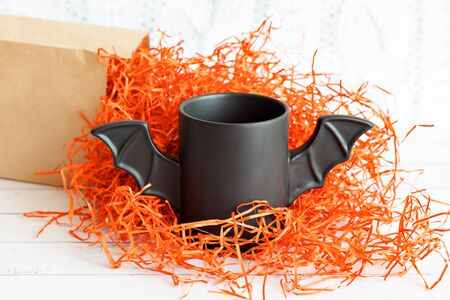 cup of coffee like a bat in a red paper packaging for Halloween. White background. Toy bat. Halloween concept.