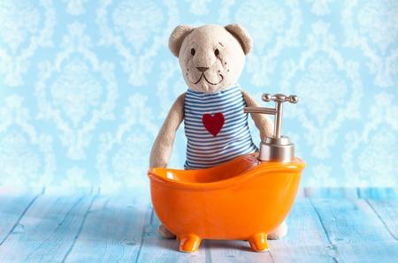 childrens soft toy teddy bear is bathed in orange bath doll house. Blue bathroom to bear. Playing with dolls in the family. To bathe in the bathroom.