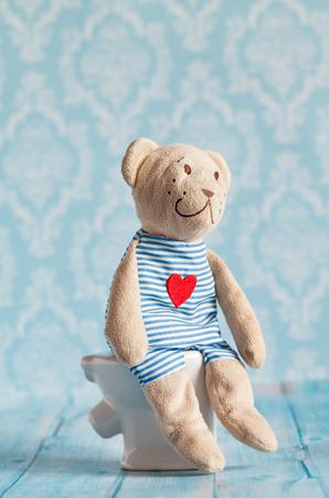 kinderen zacht speelgoed teddybeer speelgoed zittend op het toilet in het poppenhuis. Blue badkamer te dragen. Het spelen met poppen in de familie. Spijsverteringsproblemen, voedselvergiftiging. Stockfoto