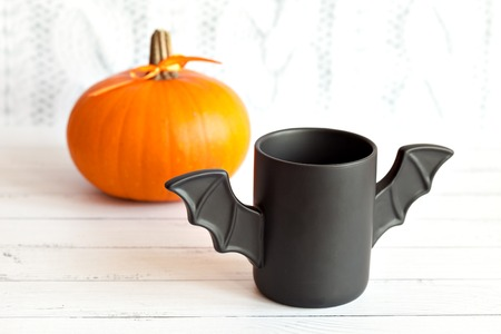cup of coffee like a bat in a red paper packaging for Halloween. White background. Toy bat and pumpkin Halloween concepts.