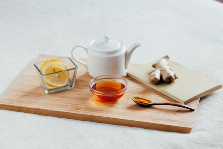 Herbal tea with chamomile flowers, turmeric and honey on a wooden board. Treatment of hot drink with ginger. Treatment of folk remedies in bed. Stock Photo