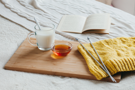 Hot milk in a glass cup and honey on a wooden board. Treatment of hot drink. Treatment of folk remedies in bed. Knitting needles and yarn for knitting. The book to read. Stock Photo