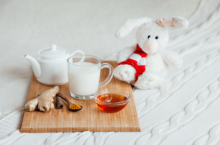 Hot milk in a glass cup and honey on a wooden board. Treatment of children a hot drink. Treatment of folk remedies in bed. Soft toy bunny for your child. Stock Photo
