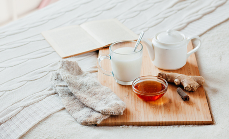Hot milk in a glass cup and honey on a wooden board. Treatment of children a hot drink. Treatment of folk remedies in bed. Warm knitted socks. The book to read.