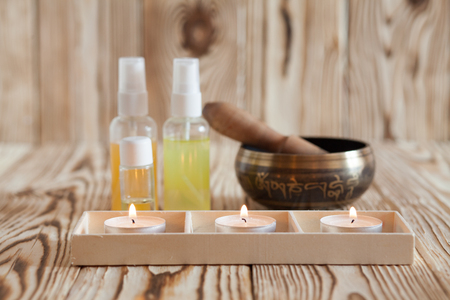 Singing bowl on wooden background. Burning candles and oil for aromatherapy and massage Stock Photo