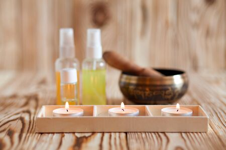 singing bowl massage: Singing bowl on wooden background. Burning candles and oil for aromatherapy and massage Stock Photo
