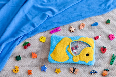Childrens toy goldfish made of colored fleece for motor development. Bag fleece filled with plastic beads and figurines on the background of scattered toys and blue fabric. handmade toys. Happy childhood.