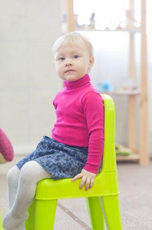 diligente: Adorable niña sentada en una silla Foto de archivo