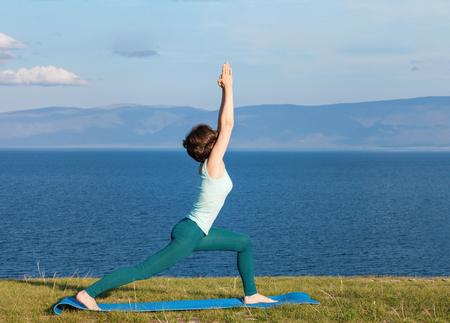 Young woman doing yoga at seaside Stockfoto