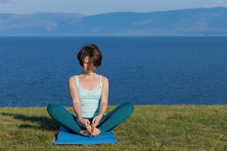 Woman meditating at seaside.