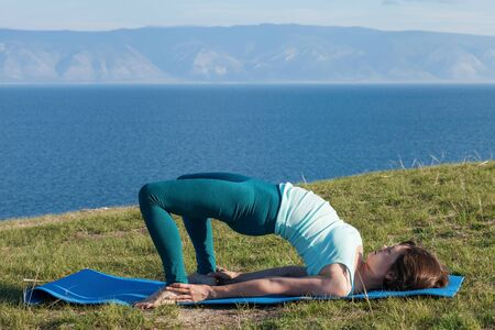 lifestyle concept - young woman making yoga exercises on beach