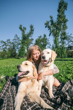 Girl with two golden retriever dogs in a park Standard-Bild - 132304454