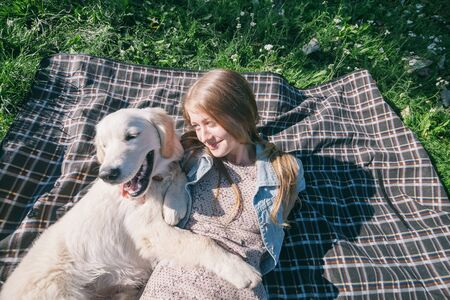 selective focus beautiful girl hugs two golden retriever and smiling sitting on a meadow Standard-Bild - 132304462
