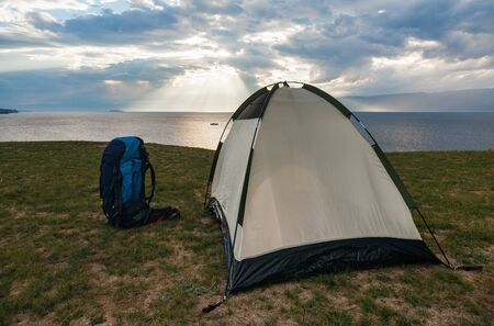 Empty tent with backpack of travelers on green terrain in bright sunset light