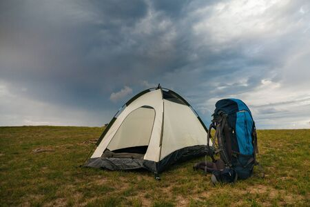 Empty tent with backpack of travelers on green terrain in bright sunset light Standard-Bild - 132304485