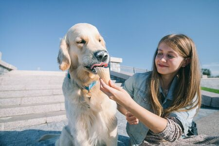 A young girl feeds her dog ice cream in a park on a hot summer day. Standard-Bild - 132304535
