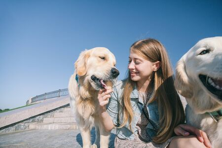 A young girl feeds her dogs ice cream in a park on a hot summer day. Standard-Bild - 132304563