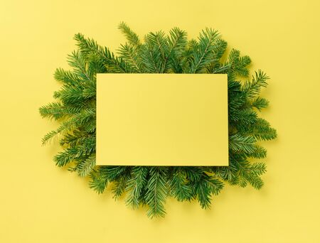 Christmas composition. Christmas decorations, paper empty on a fir branch on a yellow background. Flat lay, top view, copy space. Standard-Bild - 133051576