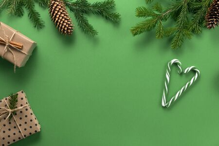 Christmas composition. Gifts, branches of spruce, cones and a lollipop cane in the shape of a heart on a green background. Christmas, winter, new year concept. Flat lounger, top view, copy space. Standard-Bild - 133174913