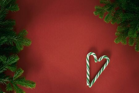 Christmas composition. Branches of spruce, lollipop cane in the shape of a heart on a red background. Christmas, winter, new year concept. Flat lay, top view, copy space Standard-Bild - 133247490
